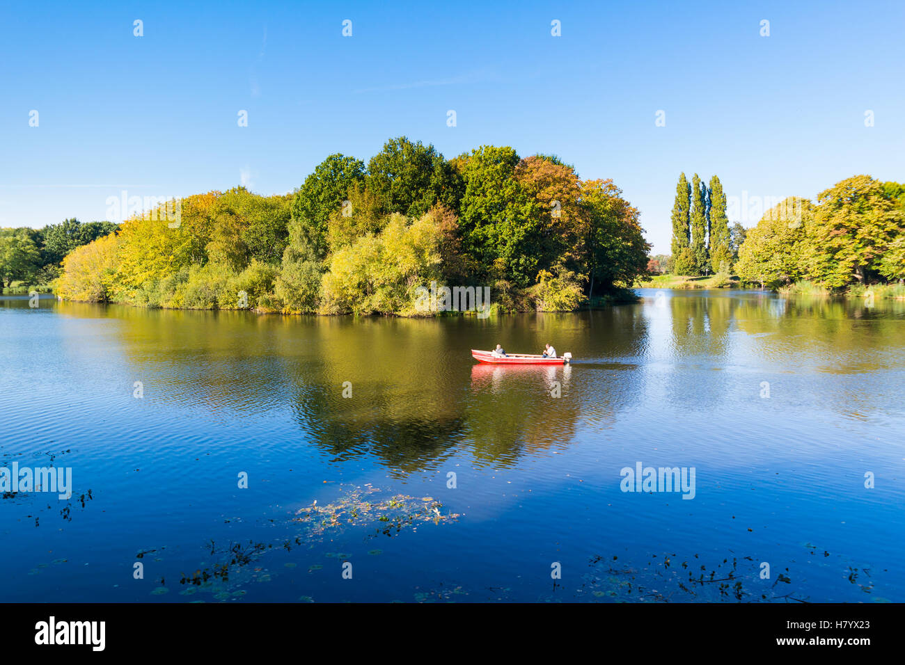 People in boat cruising on moat in autumn in old fortified town of Naarden, North Holland, Netherlands - Stock Image