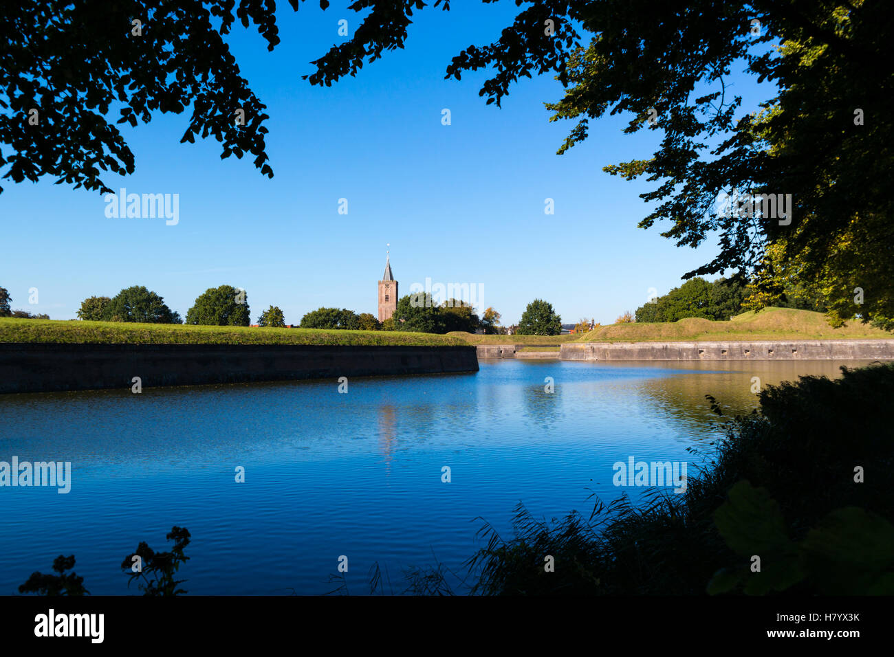 Church tower and rampart with bastion Promers of fortified town of Naarden, North Holland, Netherlands - Stock Image