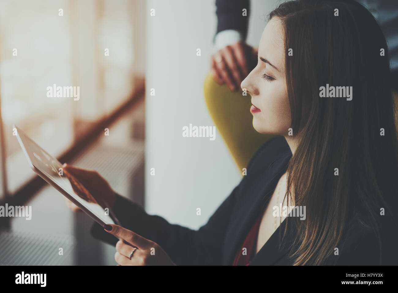 Young serious successful woman entrepreneur in formal business suite sitting with digital tablet next to window - Stock Image