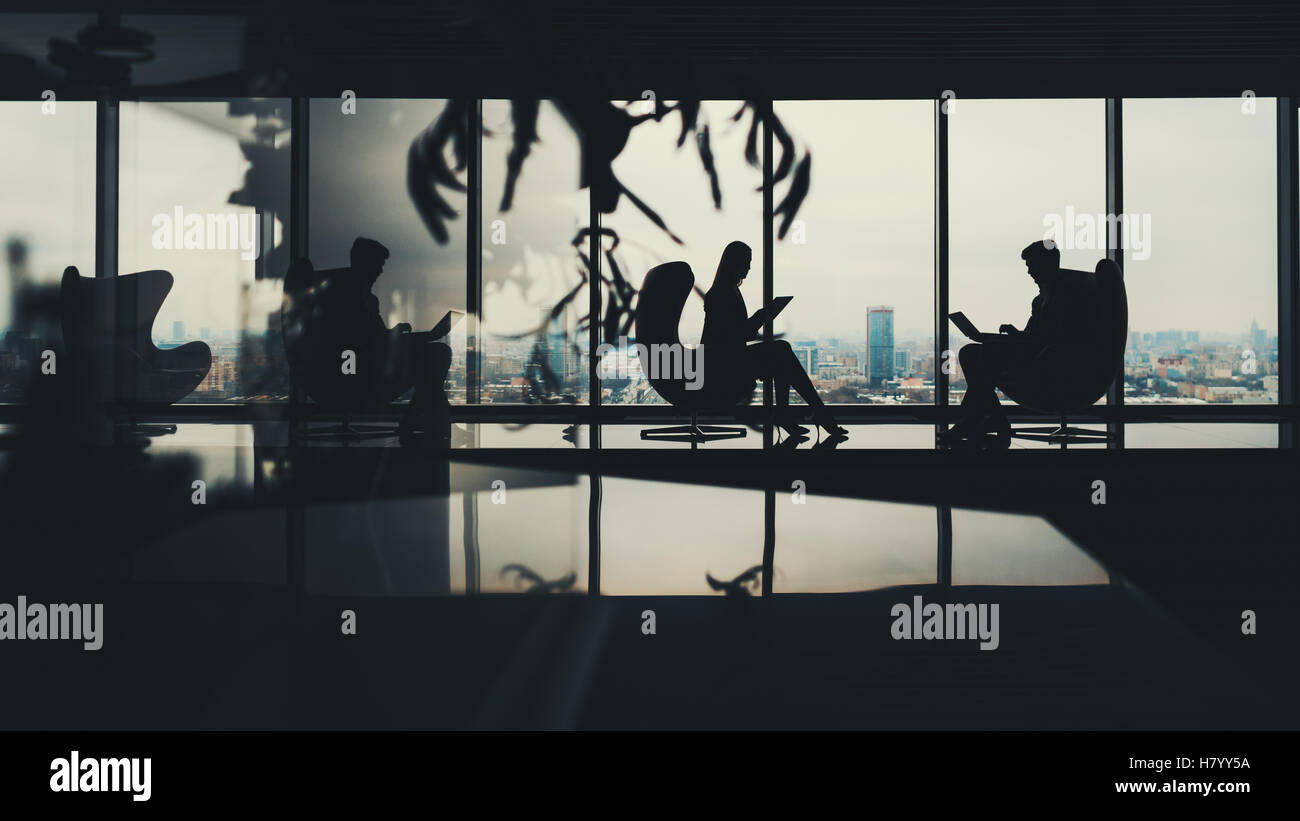 Silhouettes of two business people man and woman working on their gadgets sitting on armchairs in office interior - Stock Image