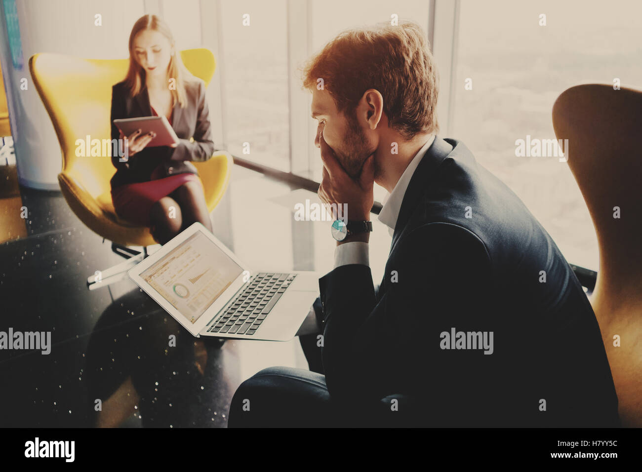 Bearded thoughtful man entrepreneur in formal business suite sitting on yellow armchair with laptop with diagrams - Stock Image