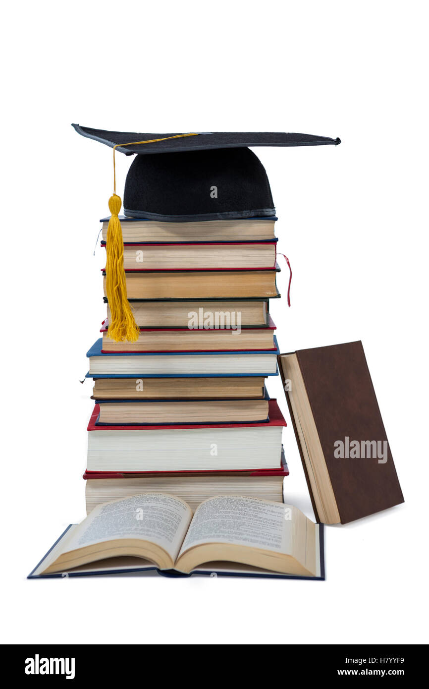 Mortarboard on stack of books - Stock Image