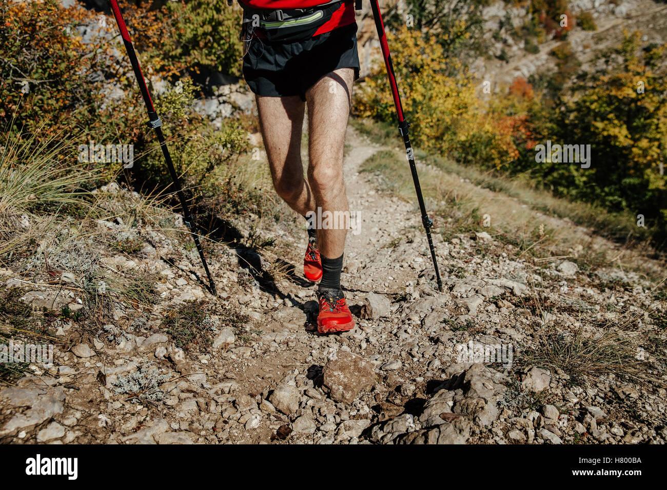 closeup feet  runner athlete and walking sticks on a mountain trail Stock Photo