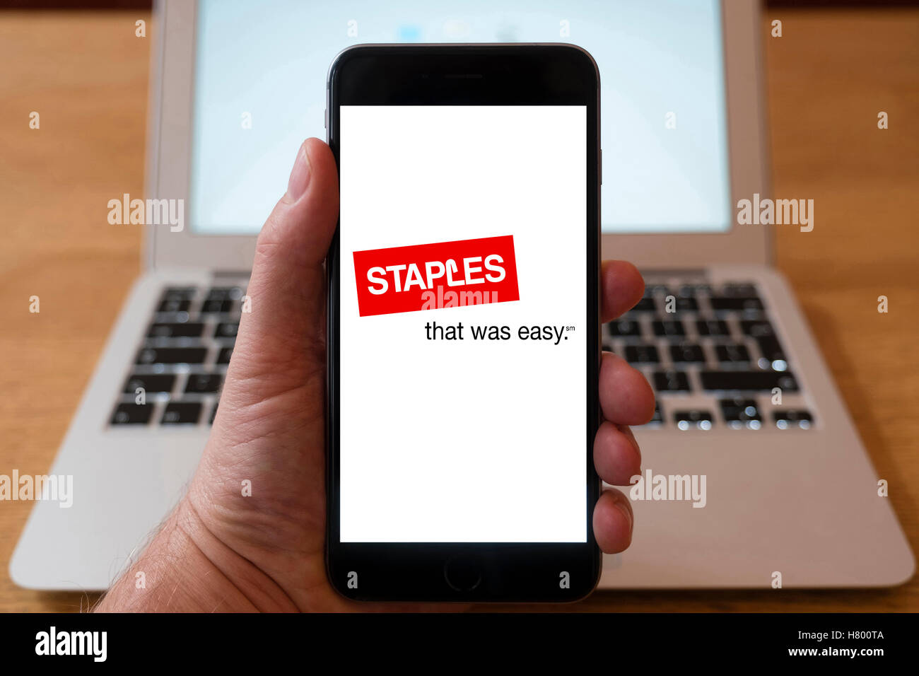 Using iPhone smartphone to display logo of Staples office supplies chain of stores - Stock Image