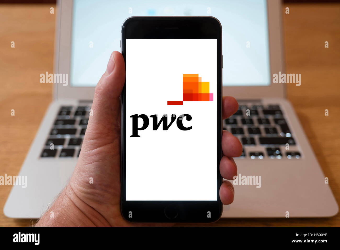 Using iPhone smartphone to display logo of PWC , PricewaterhouseCoopers , the multinational professional services - Stock Image