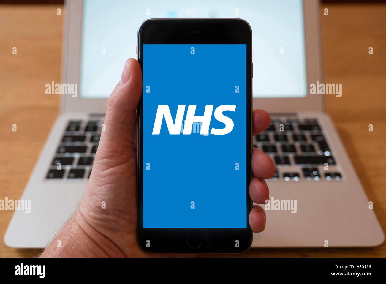 Using iPhone smartphone to display logo of NHS , National Health Service website Stock Photo