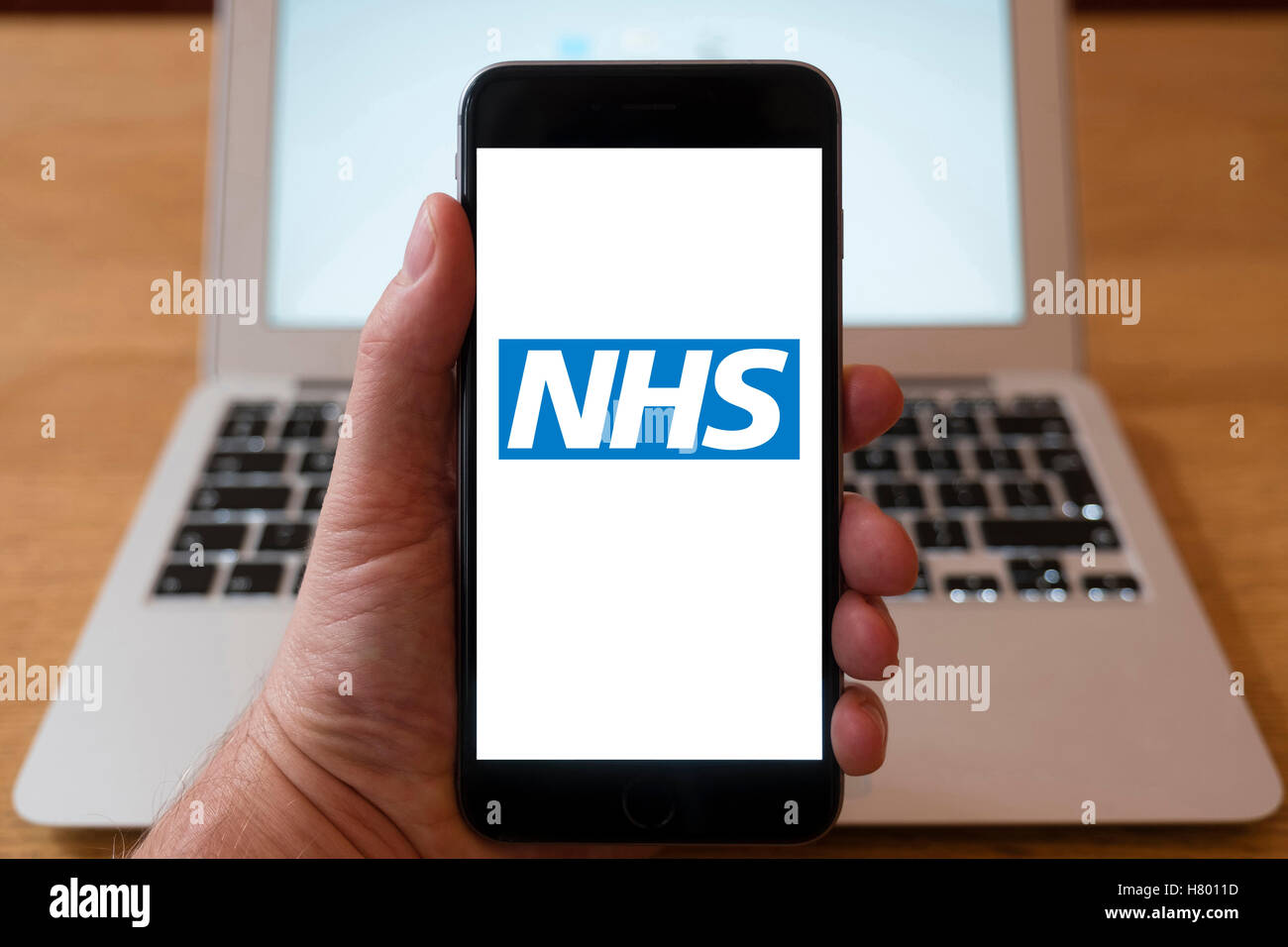 Using iPhone smartphone to display logo of NHS , National Health Service website - Stock Image