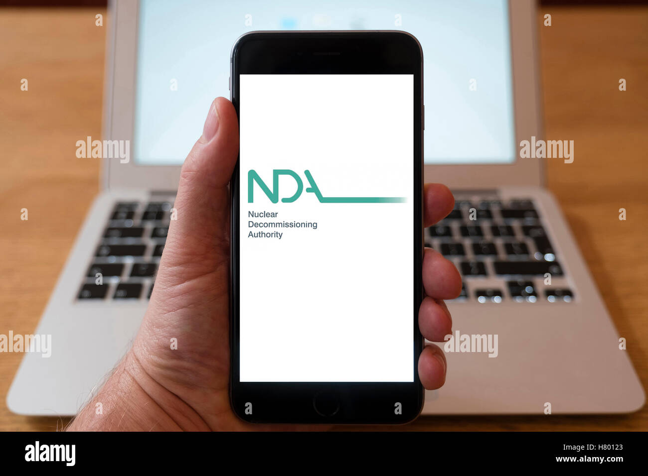 Using iPhone smartphone to display logo of Nuclear Decommissioning Authority in the UK - Stock Image