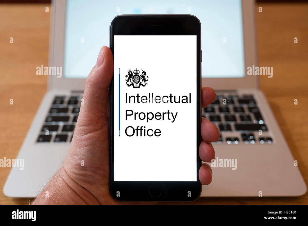 Using iPhone smartphone to display logo of UK Intellectual Property Office - Stock Image