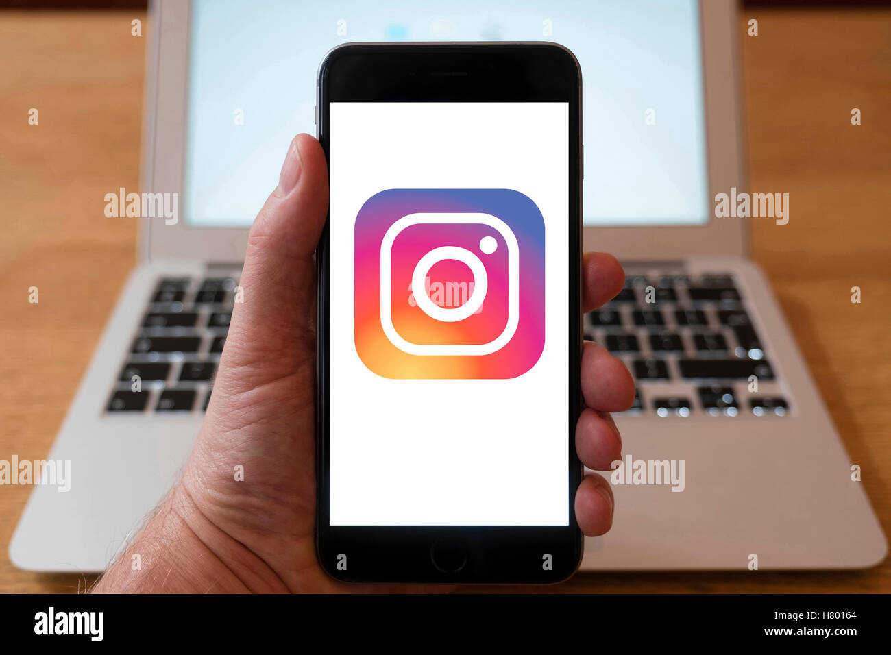 Using iPhone smartphone to display logo of Instagram, social media and photo sharing service - Stock Image