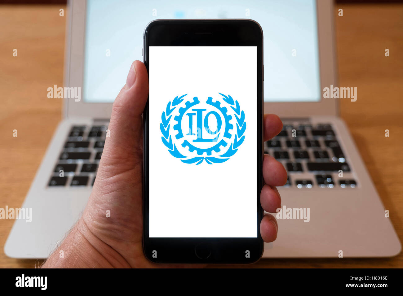 Using iPhone smartphone to display logo of ILO, International Labour Organization. UN agency to set labour standards. - Stock Image