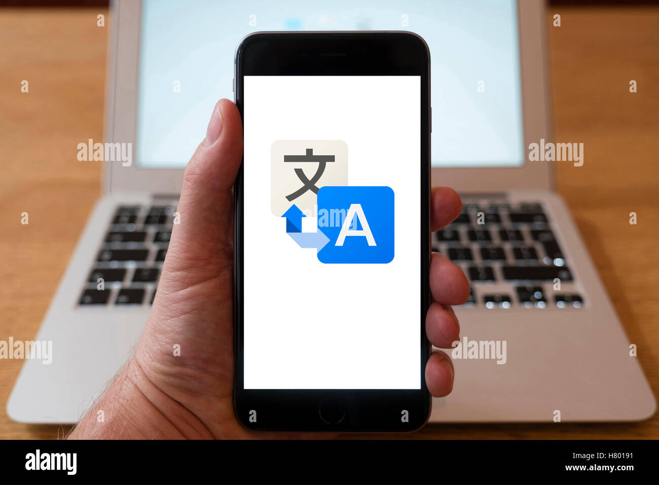 Using iPhone smartphone to display logo of Google Translate online translation service - Stock Image