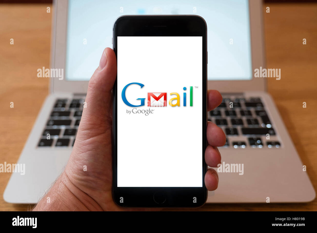 Using iPhone smartphone to display logo of Gmail , the Google email service - Stock Image