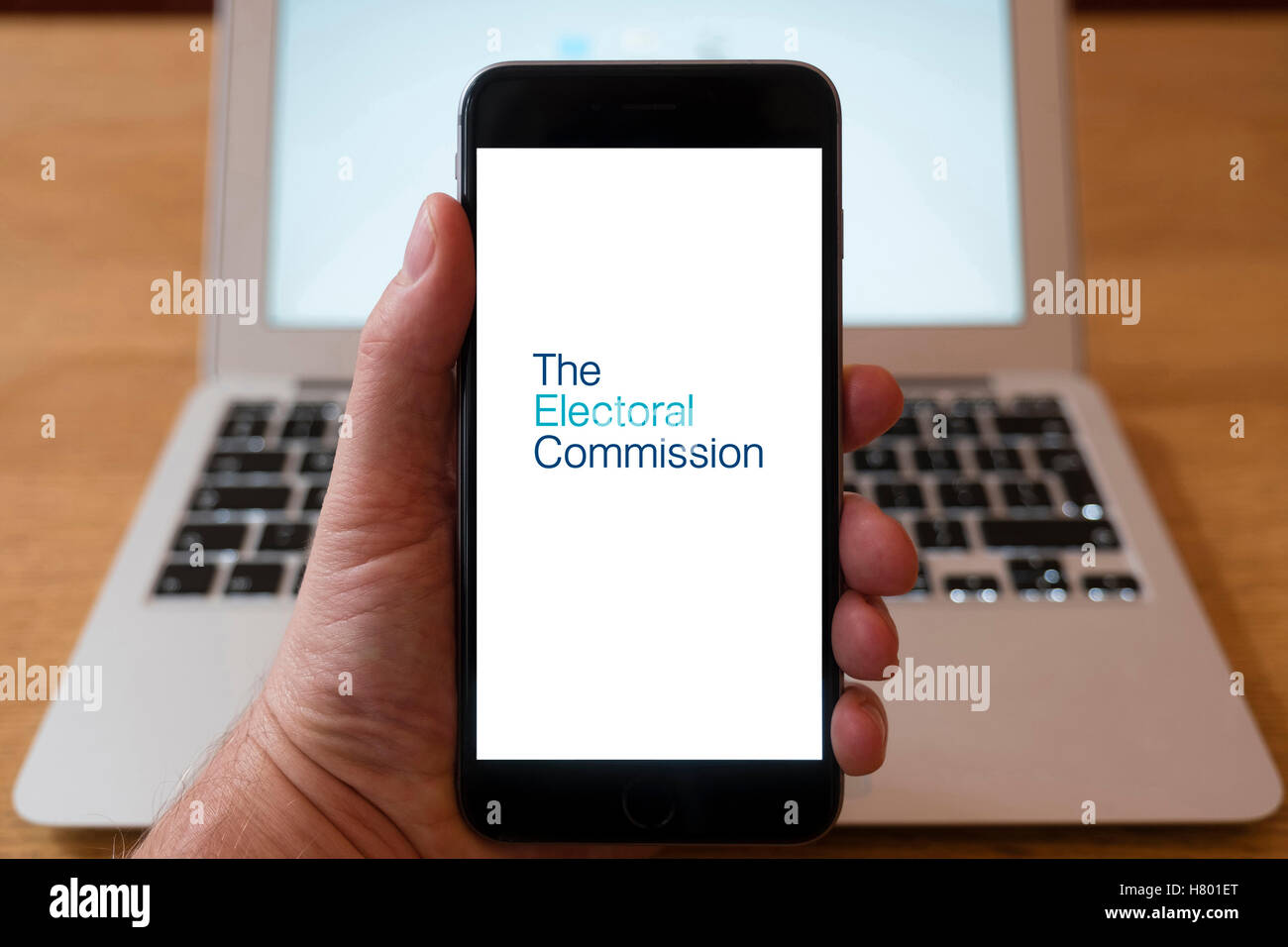 Using iPhone smartphone to display logo of The Electoral Commission Stock Photo