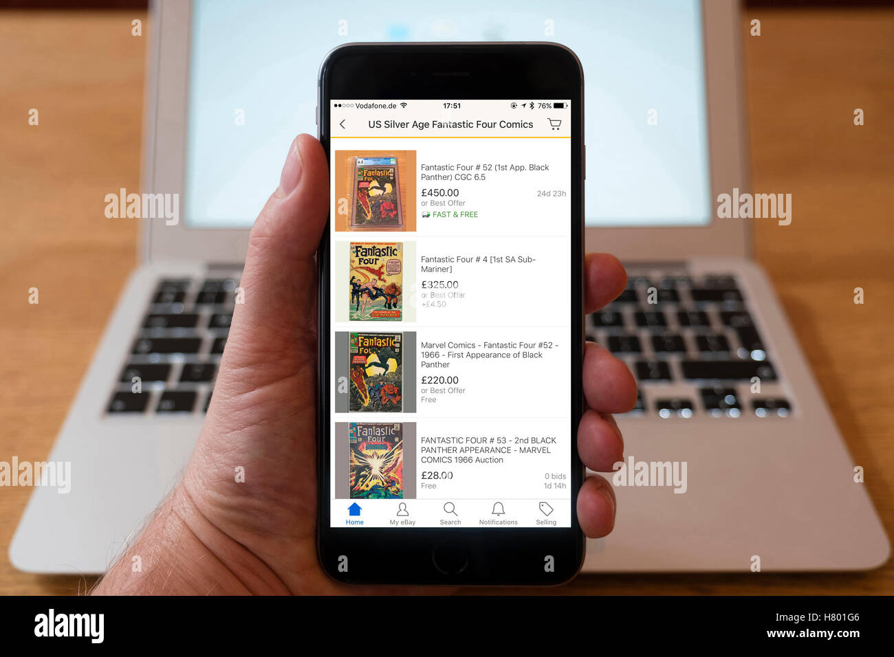 Using iPhone smartphone to display collectible comics for auction and sale on eBay - Stock Image