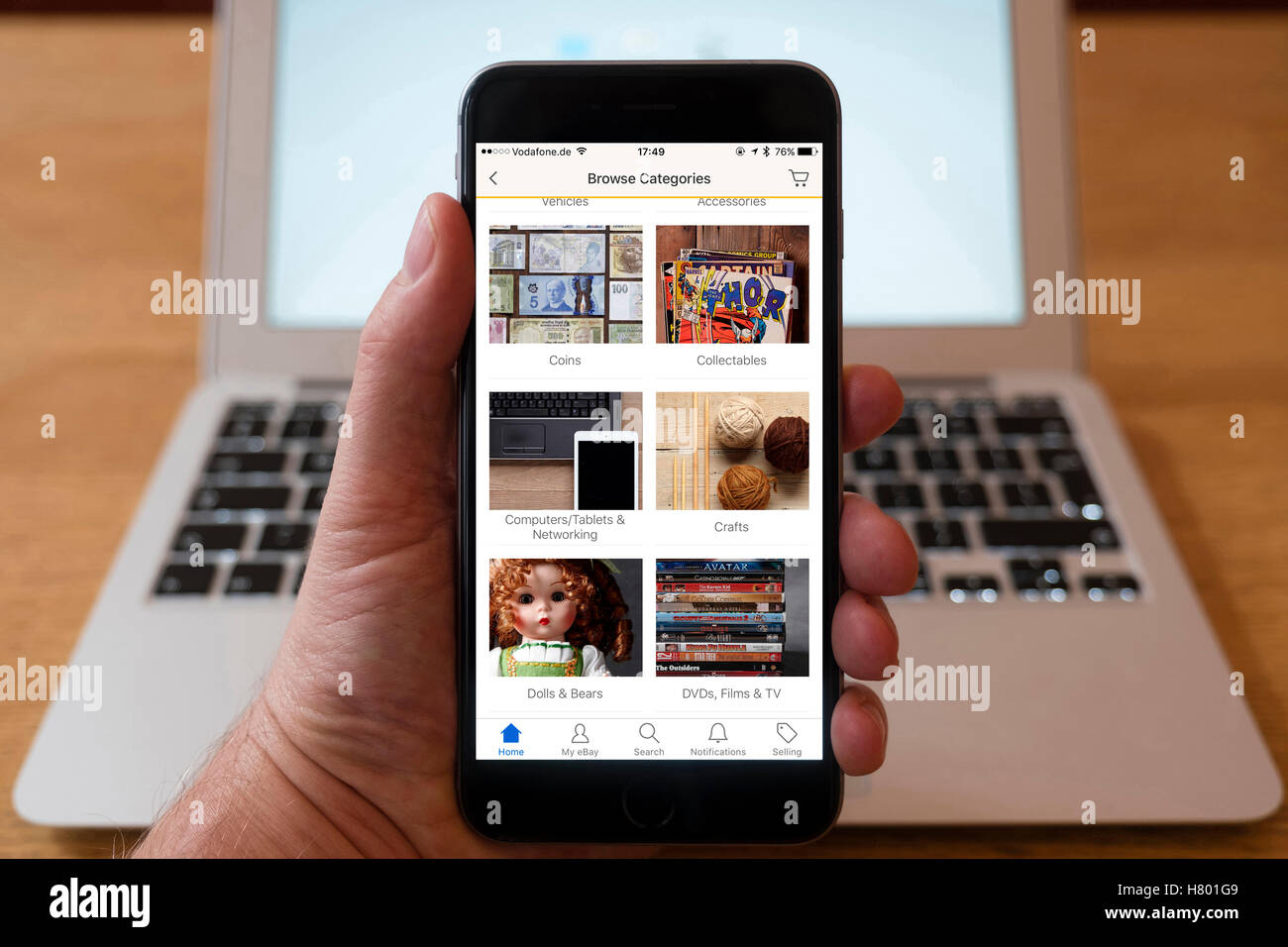 Using iPhone smartphone to display categories of products for auction and sale on eBay - Stock Image