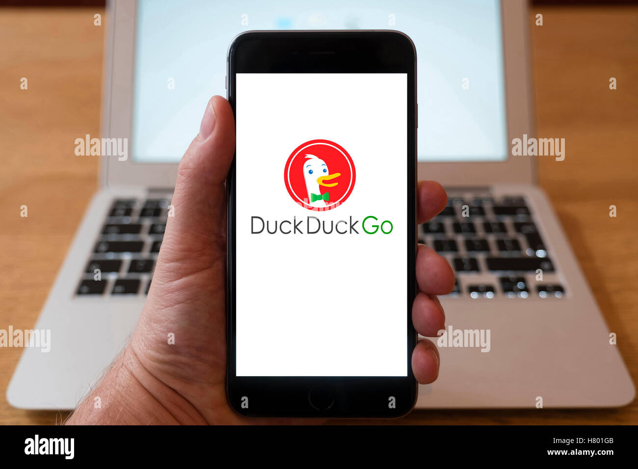 Using iPhone smartphone to display logo of Duck Duck Go search engine portal - Stock Image