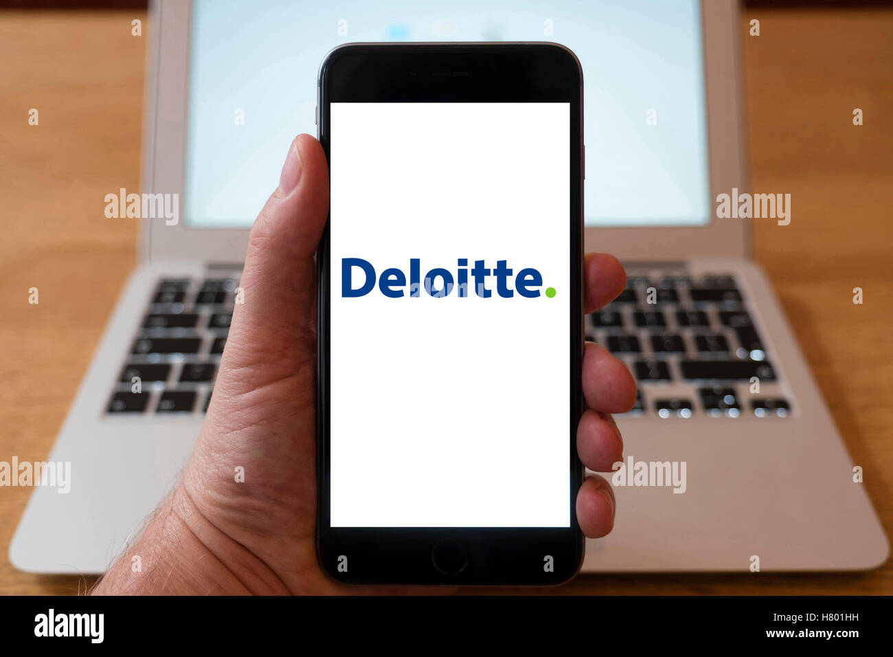 Using iPhone smartphone to display logo of Deloitte financial service company - Stock Image