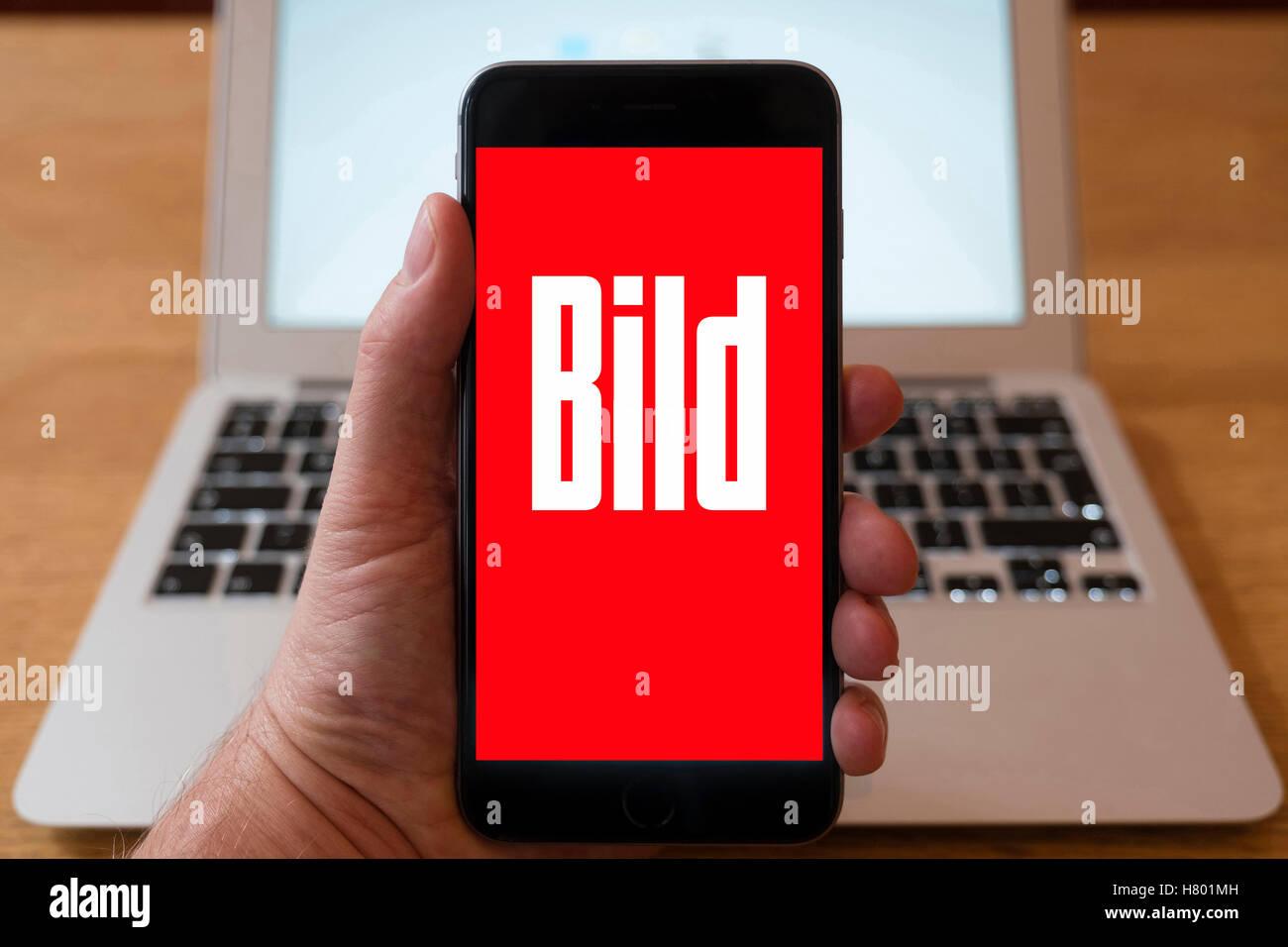 Using iPhone smartphone to display logo of Bild German tabloid magazine - Stock Image