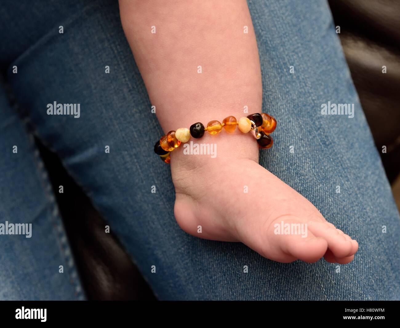A babies teething beaded bracelet made of Amber stone - Stock Image
