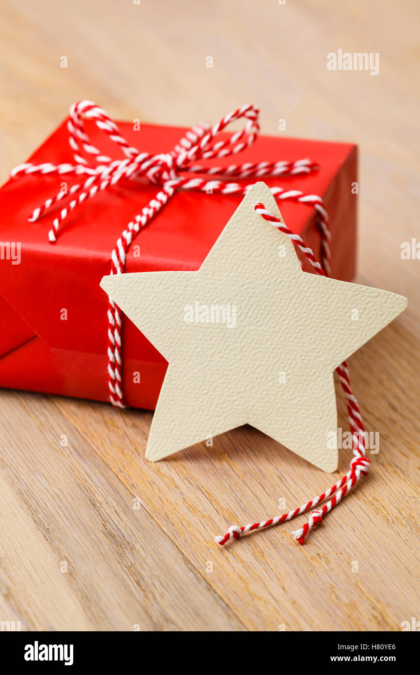 Simple Classic Red Christmas Gift Present With Handmade Blank Tag On Rustic Wood Vertical Background