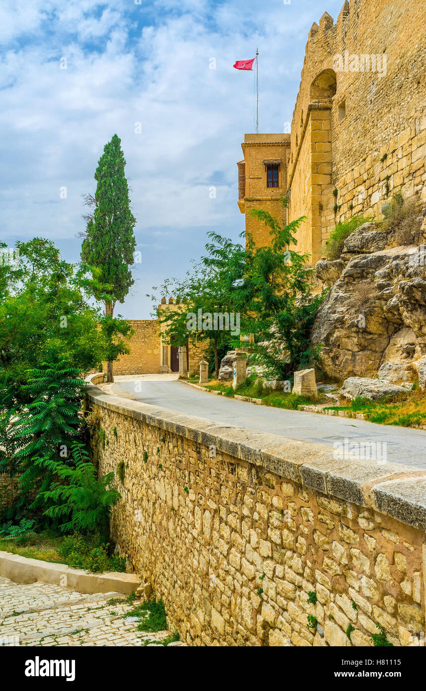 The narrow way among the stone walls and greenery leads to the Kasbah of El Kef, Tunisia. - Stock Image