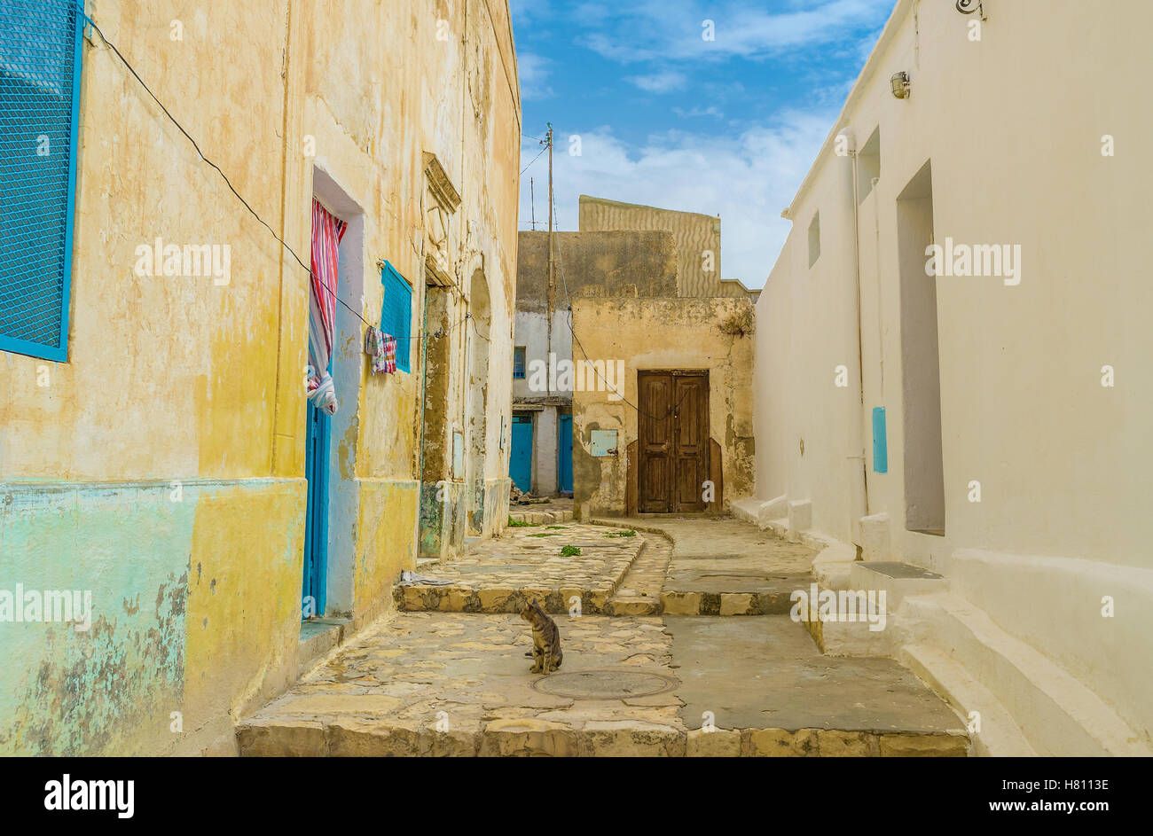The small yard in old residential neighborhood of El Kef with crumbling walls and wooden doors, Tunisia. - Stock Image