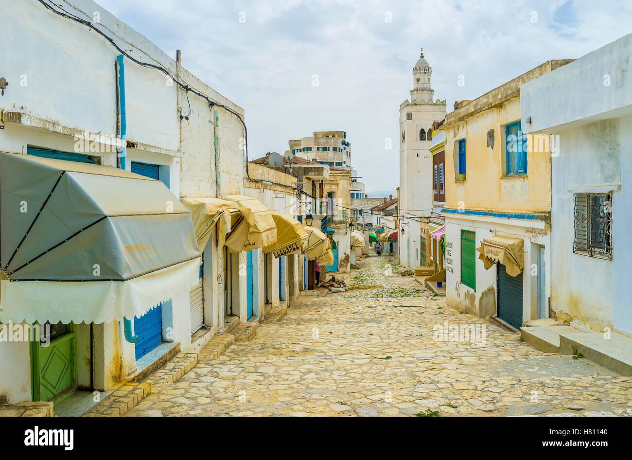 The working neighborhood with numerous workshops and stalls with the high white minaret on background, El Kef - Stock Image