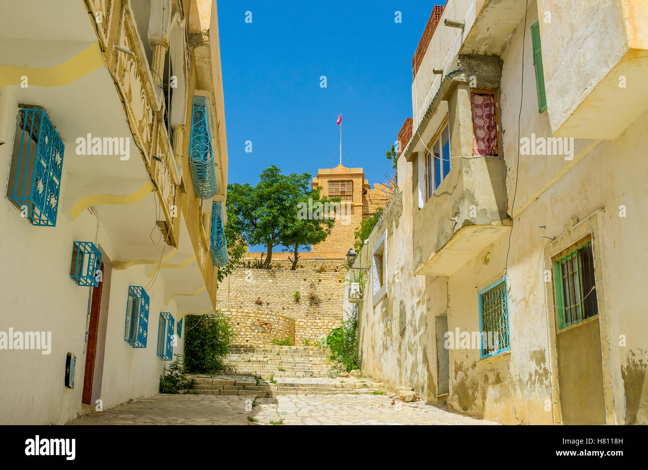 The hilly street with the high ramparts of the local Kasbah, the old fortress with preserved castle, El Kef, Tunisia. - Stock Image