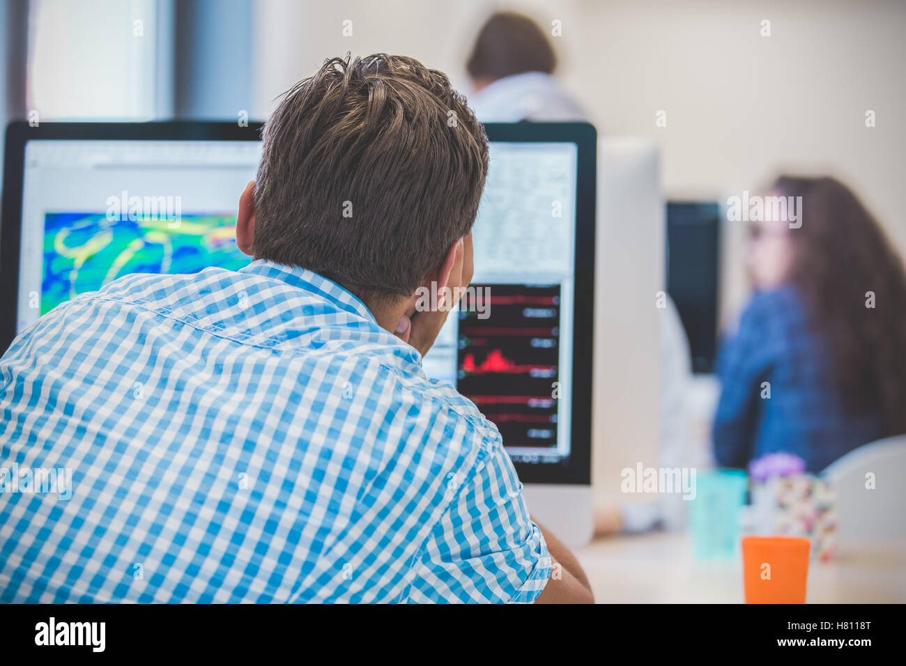 Thoughtful young programmer coding on computer - Stock Image