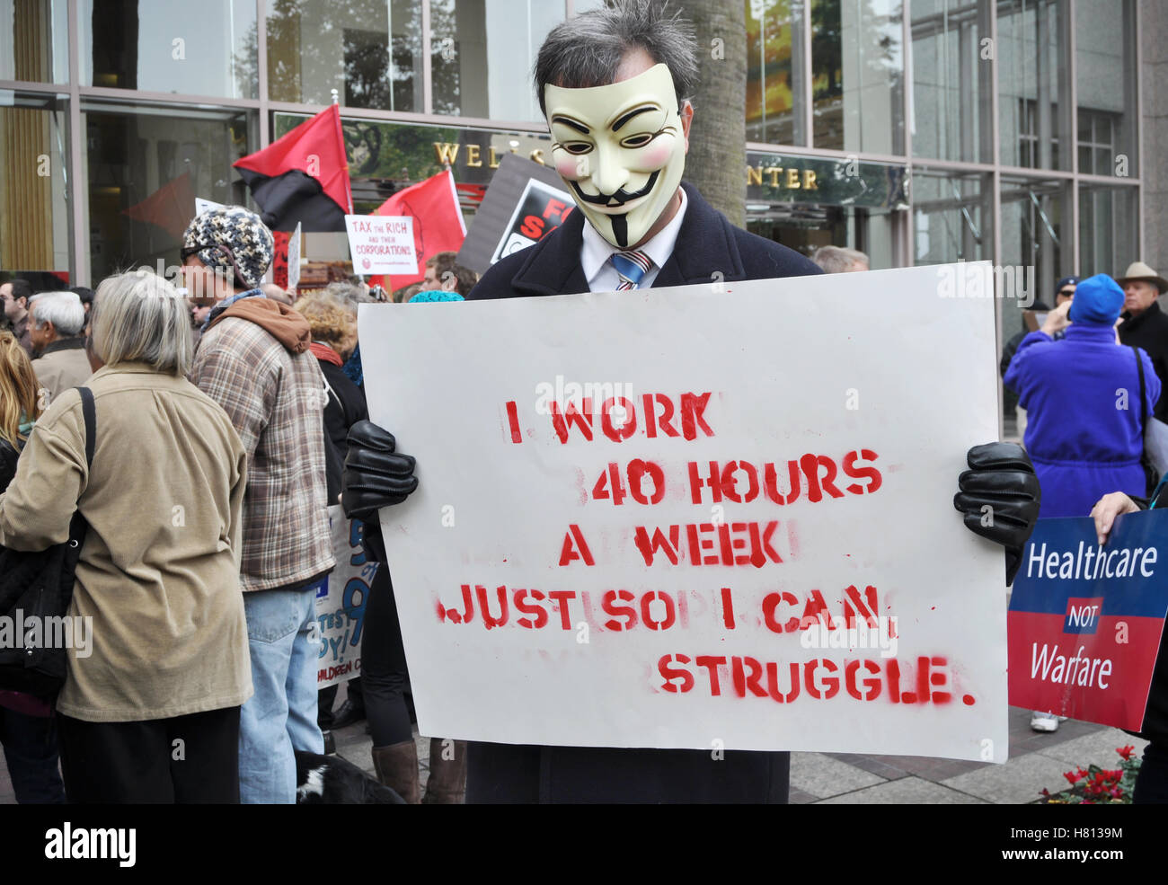 A protester in a Guy Fawkes mask holds a sign reading' I work 40 hours a week just to struggle' at a bank - Stock Image