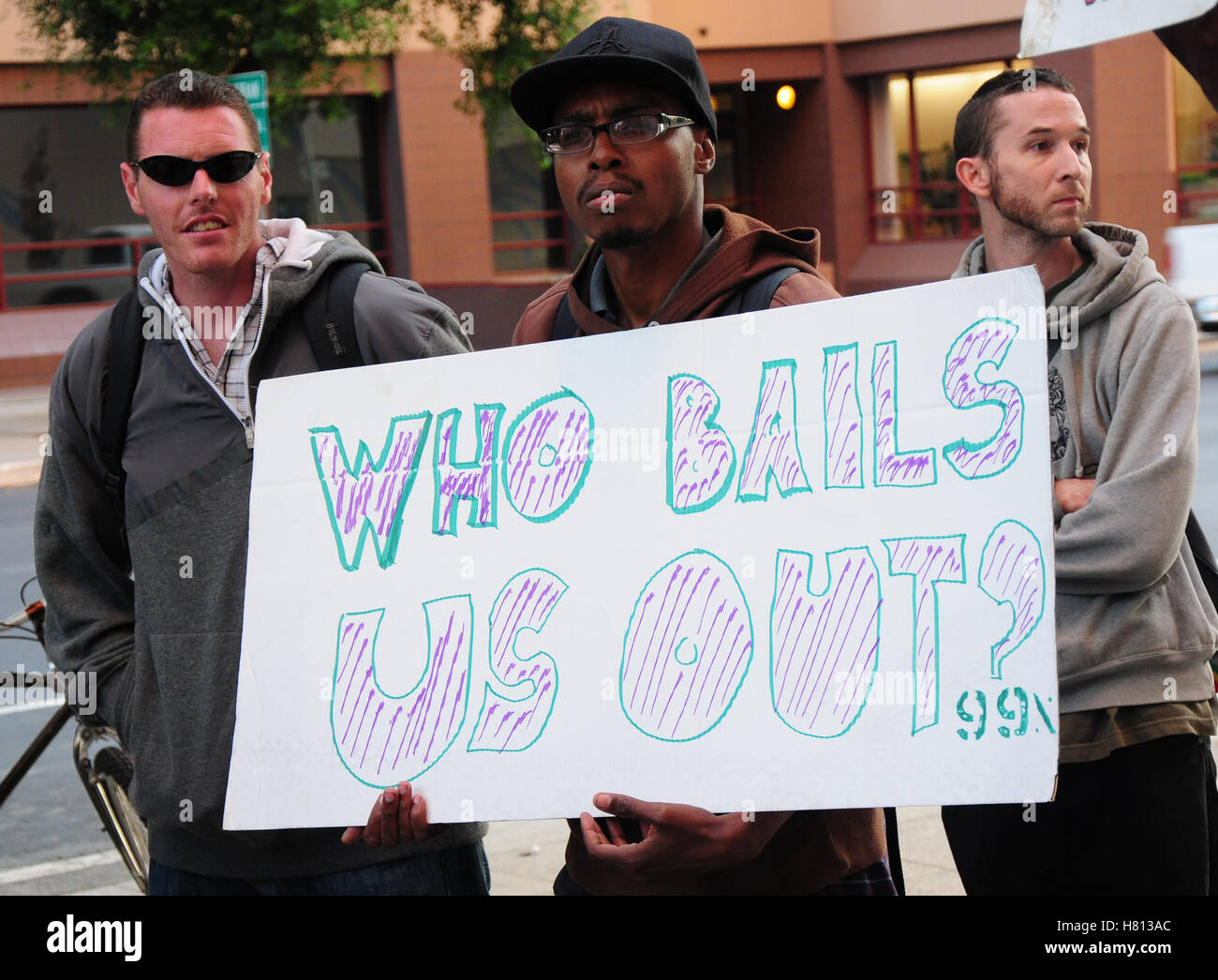 A activist holding a sign reading 'who bails us out 99%' at a march against the big wall street bailout. - Stock Image