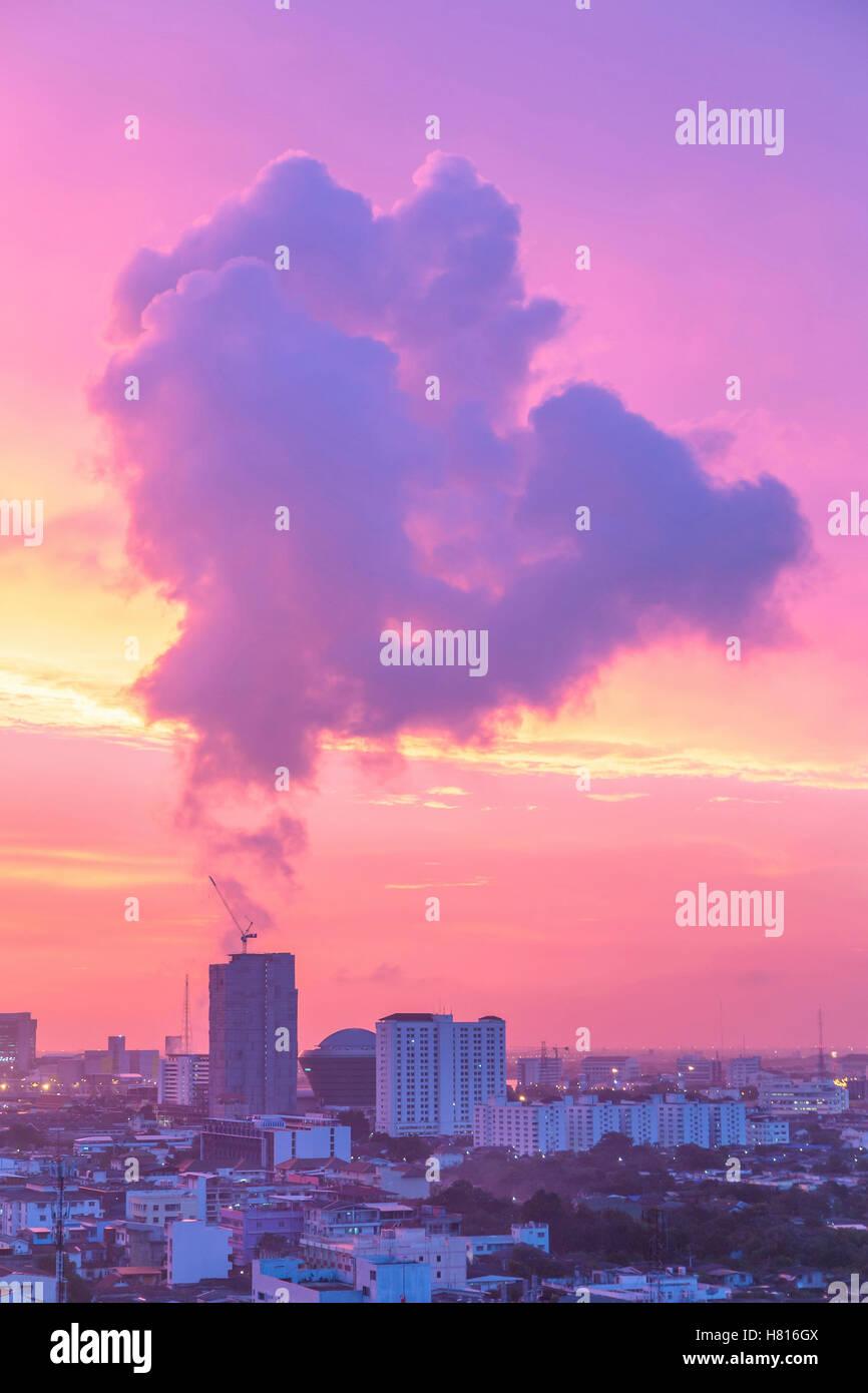 Strange smoke floating over building in Bangkok during twilight after sunset. - Stock Image