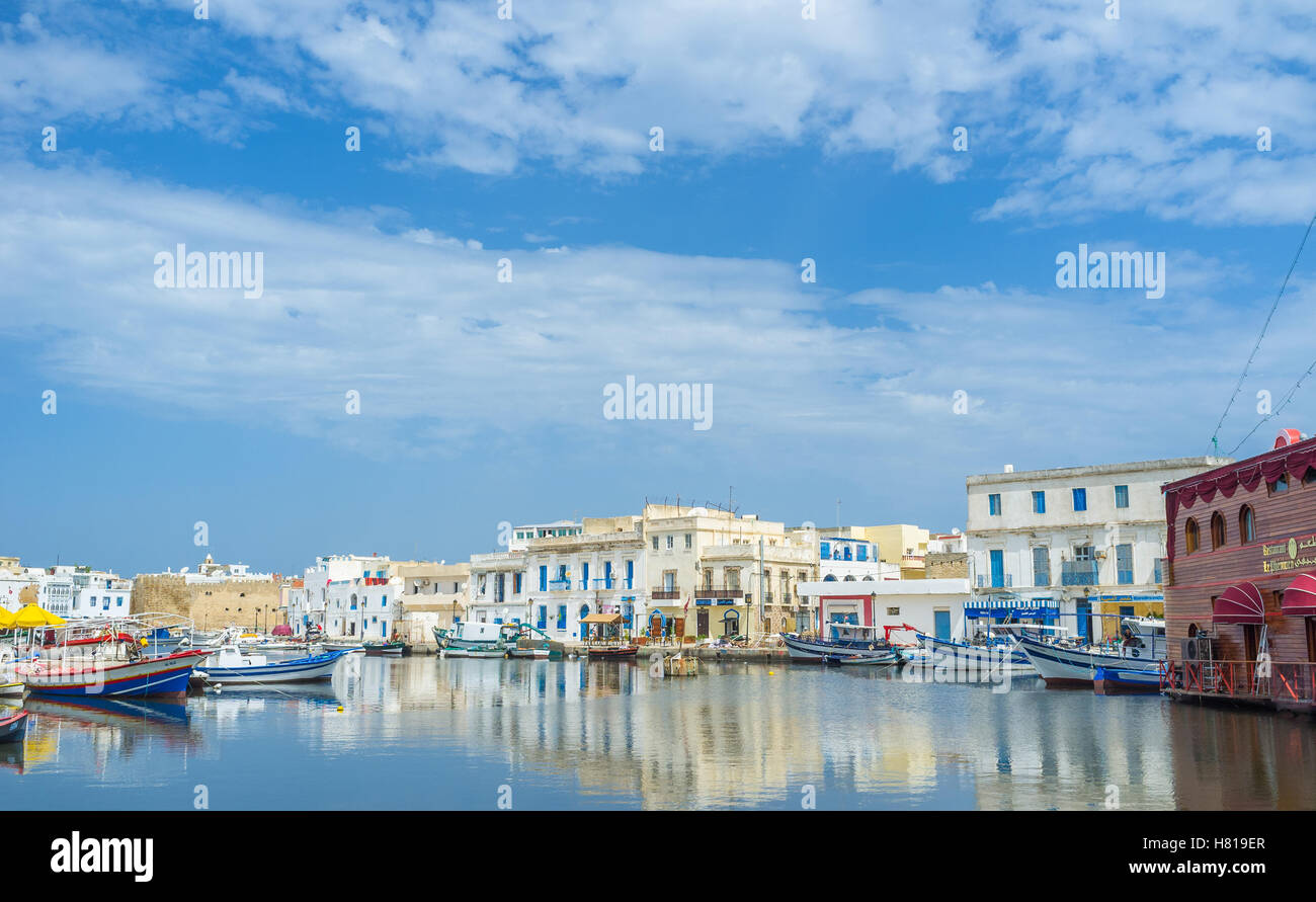 The beautiful reflection of the old town's buildings in calm water of the fishing port - Stock Image