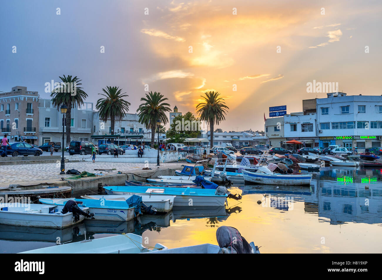 The beautiful sunset over the old port reflects in water Stock Photo