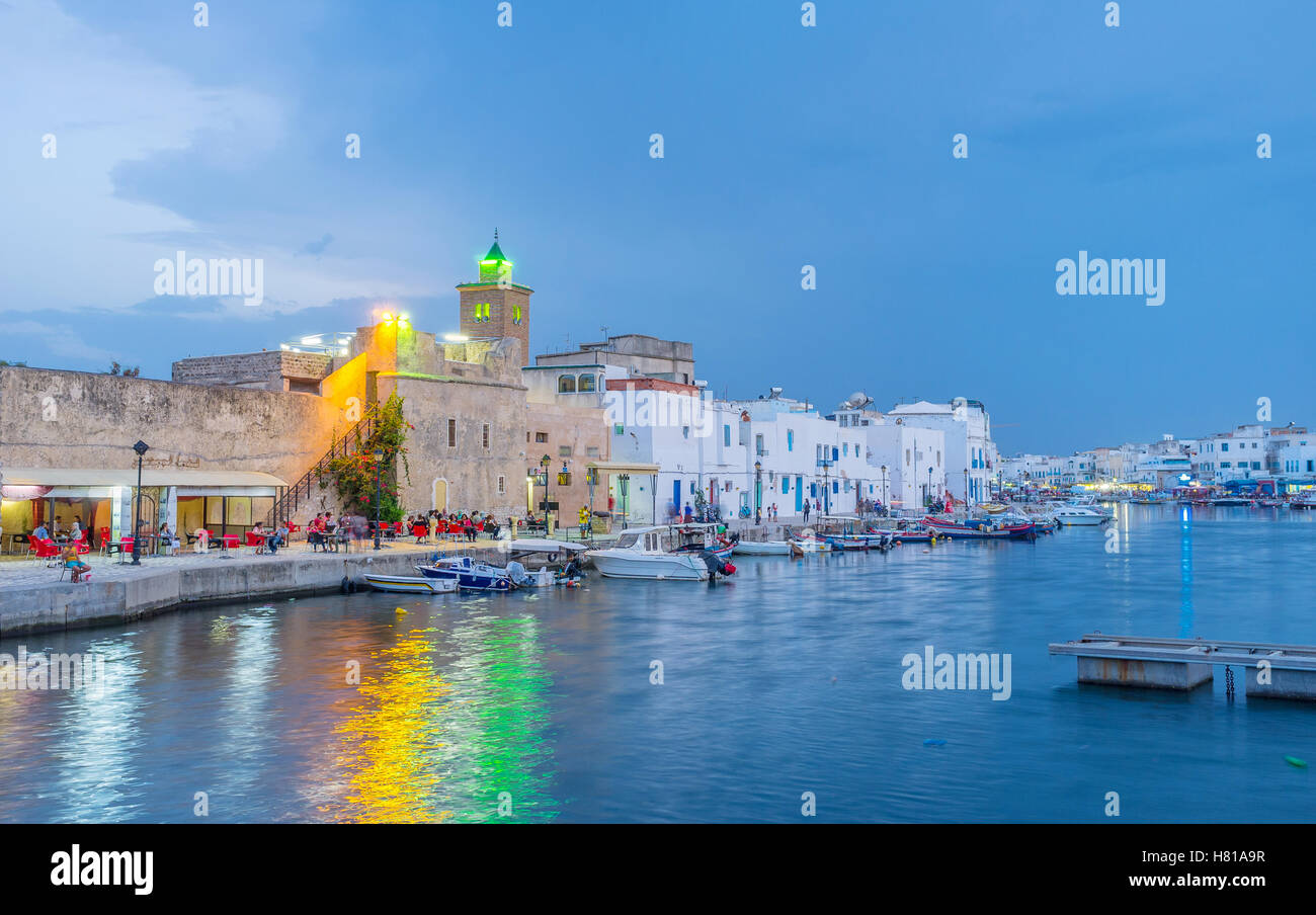 The evening Bizerte illuminated with the colorful lights, that reflect in dark water - Stock Image