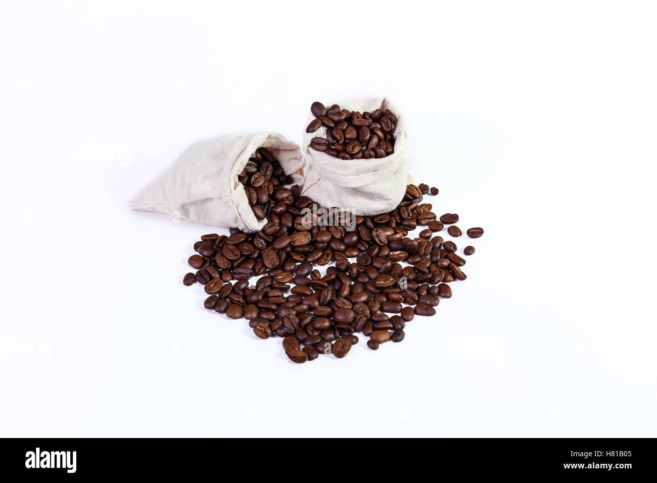 roasted coffee beans in a rag bags, roasted coffee beans on a white background. - Stock Image