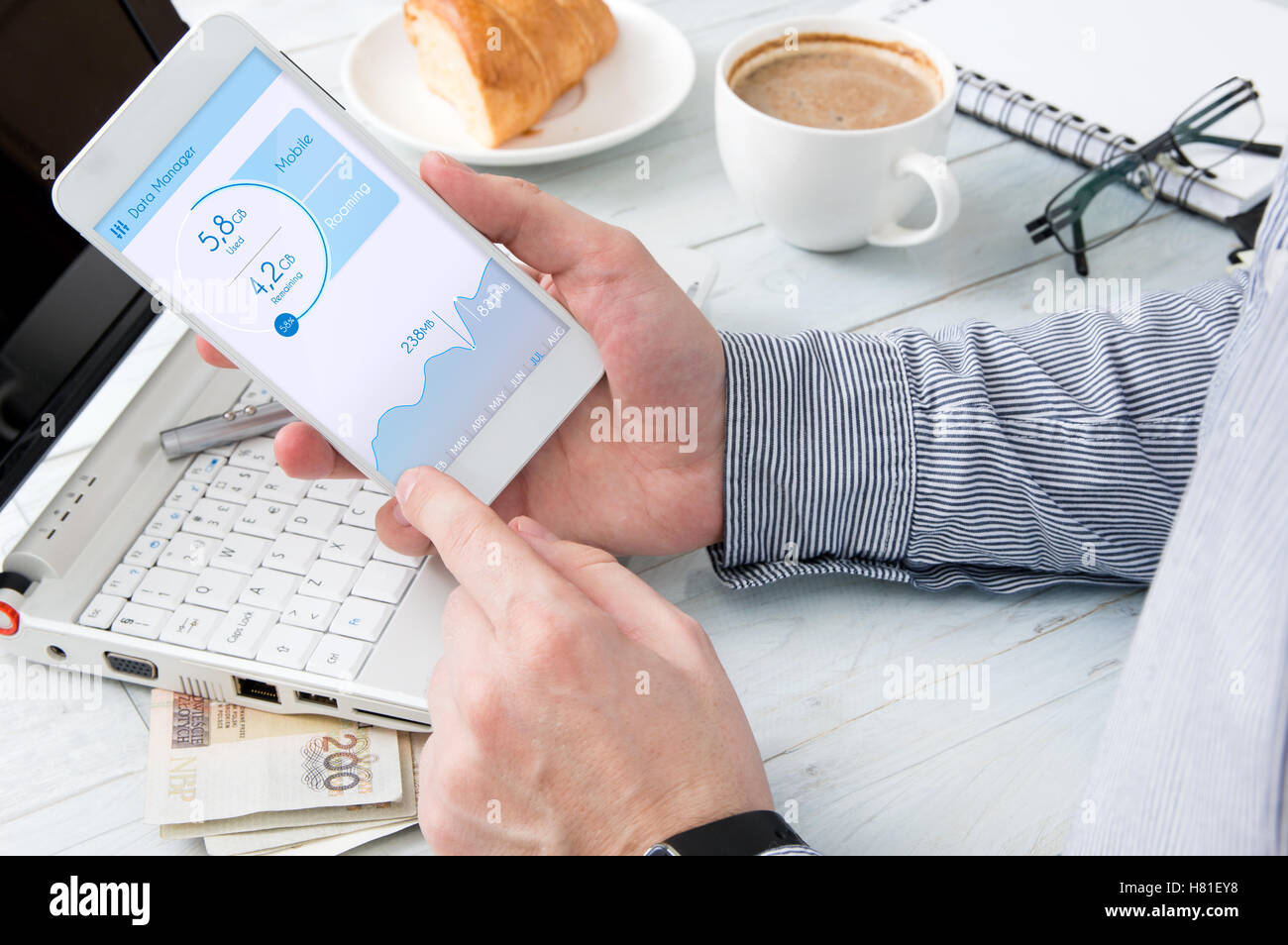 Man is checking data usage on his smartphone - Stock Image