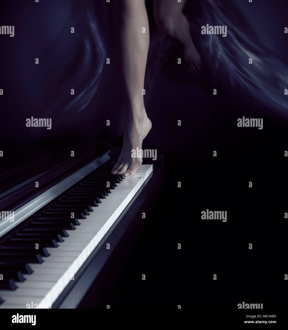 Woman bare legs dancing on a piano keyboard, music and dance artistic dream-like concept - Stock Image
