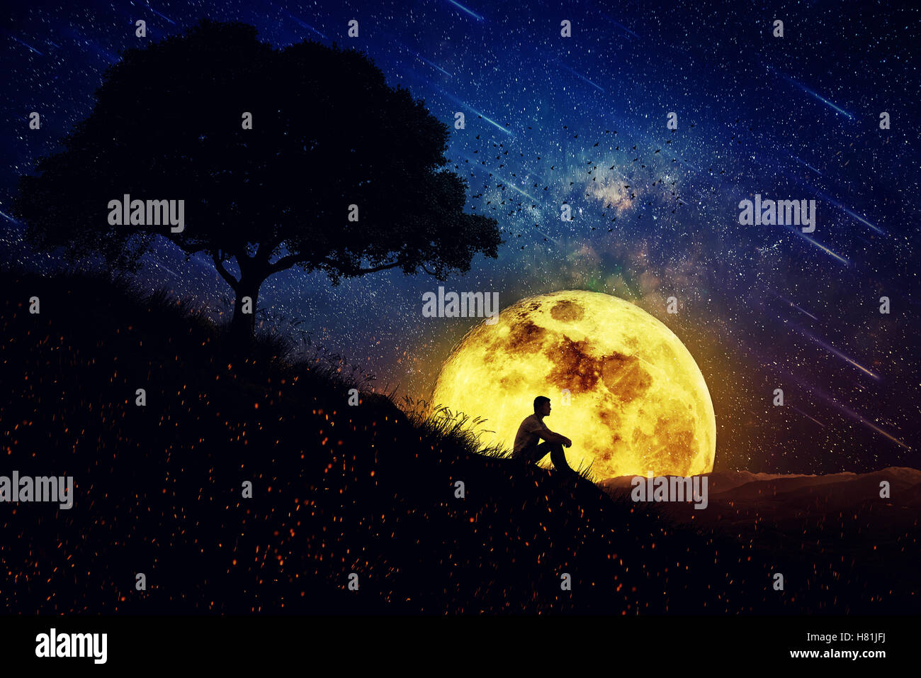 Boy sit alone on a hill in the center of nature over a full moon night background standing away from the crowd waiting for th