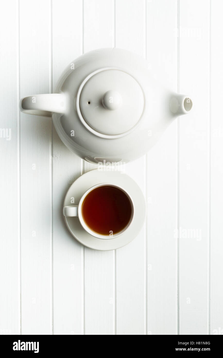 A cup of black tea and teapot on white table. Top view. - Stock Image