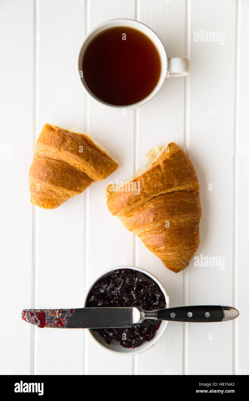 Tasty buttery croissant, cup of black tea and jam in jar. Top view. - Stock Image