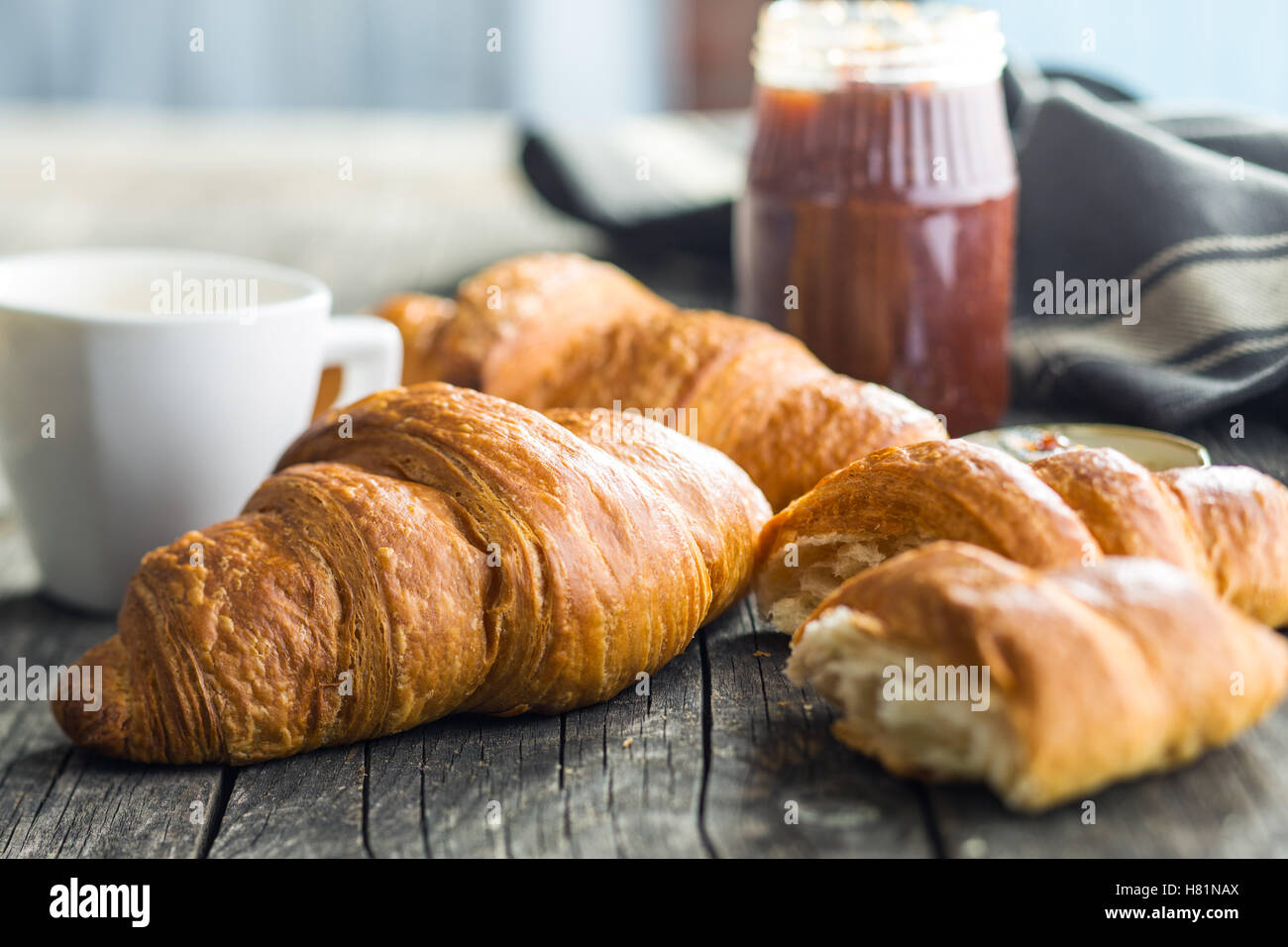 Tasty buttery croissants on old wooden table. - Stock Image