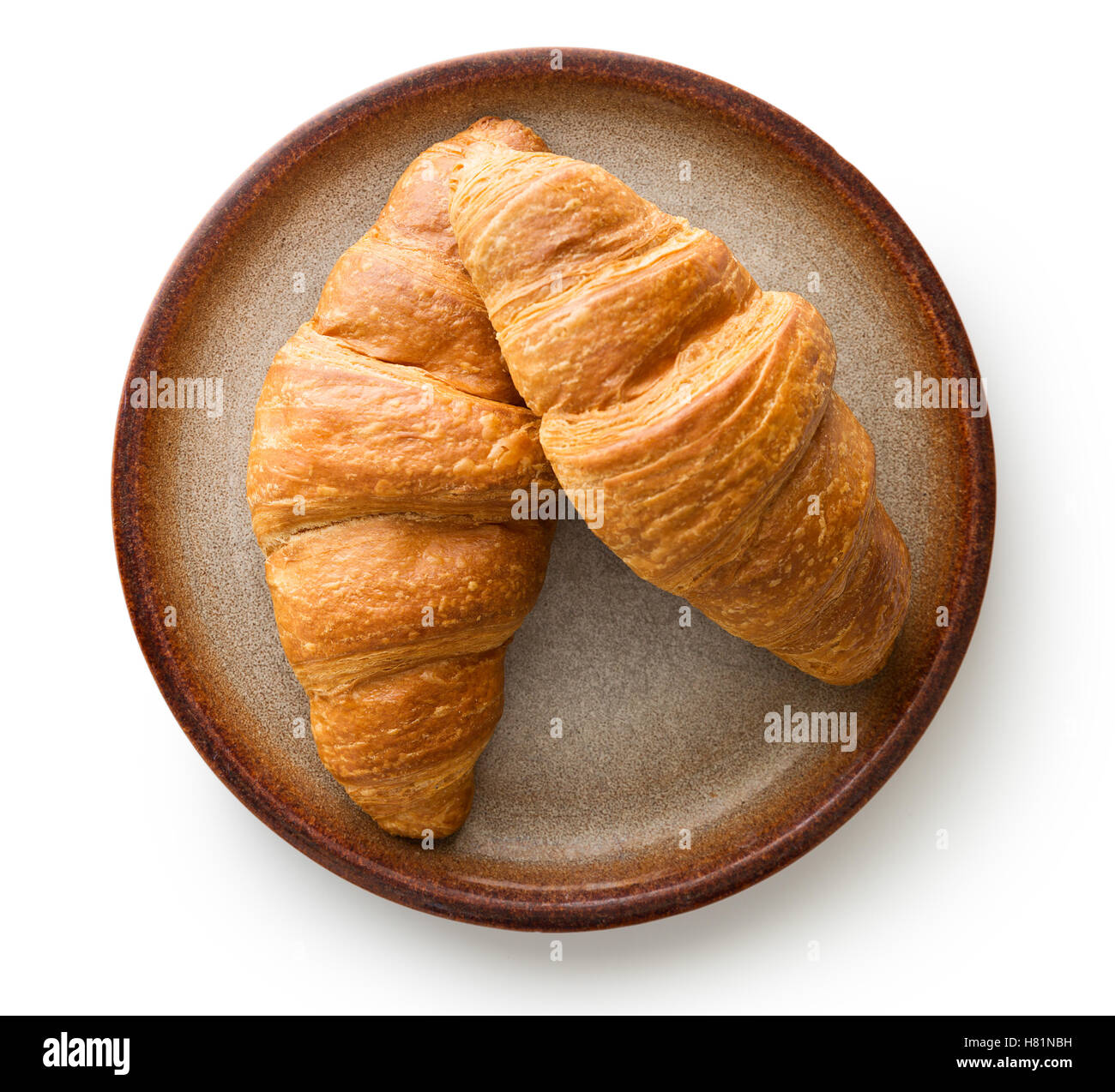 Tasty buttery croissants on plate. Isolated on white background. - Stock Image