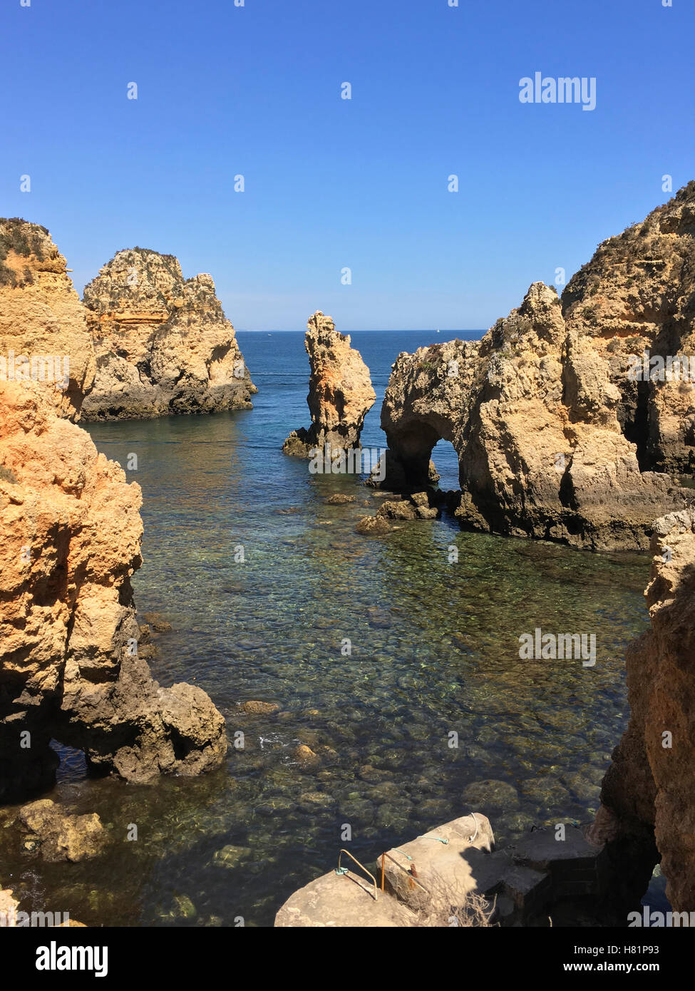 Old rocky outcroppings surrounded by low tide with calm ocean in background. Includes space for boat or copy. - Stock Image