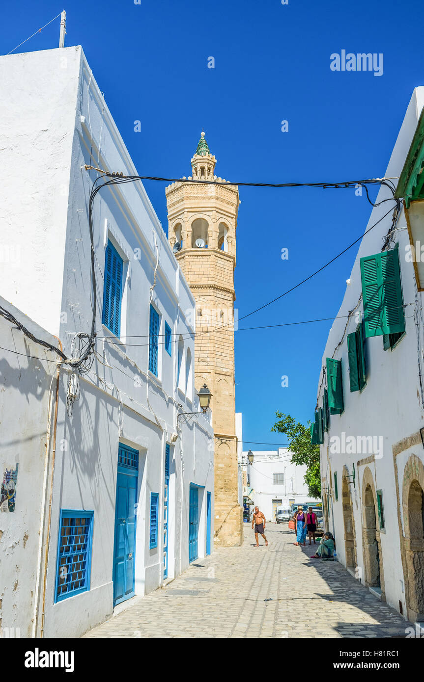 The old streets of Medina consists of the same white houses and the only difference is the minaret on background, - Stock Image