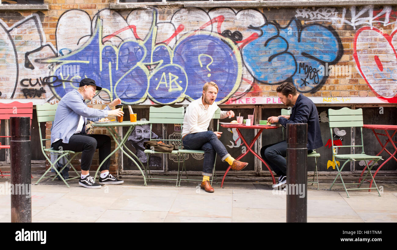 Young men having a brunch sitting outside in front of a wall covered in graffiti in the cool area of Shoreditch, - Stock Image