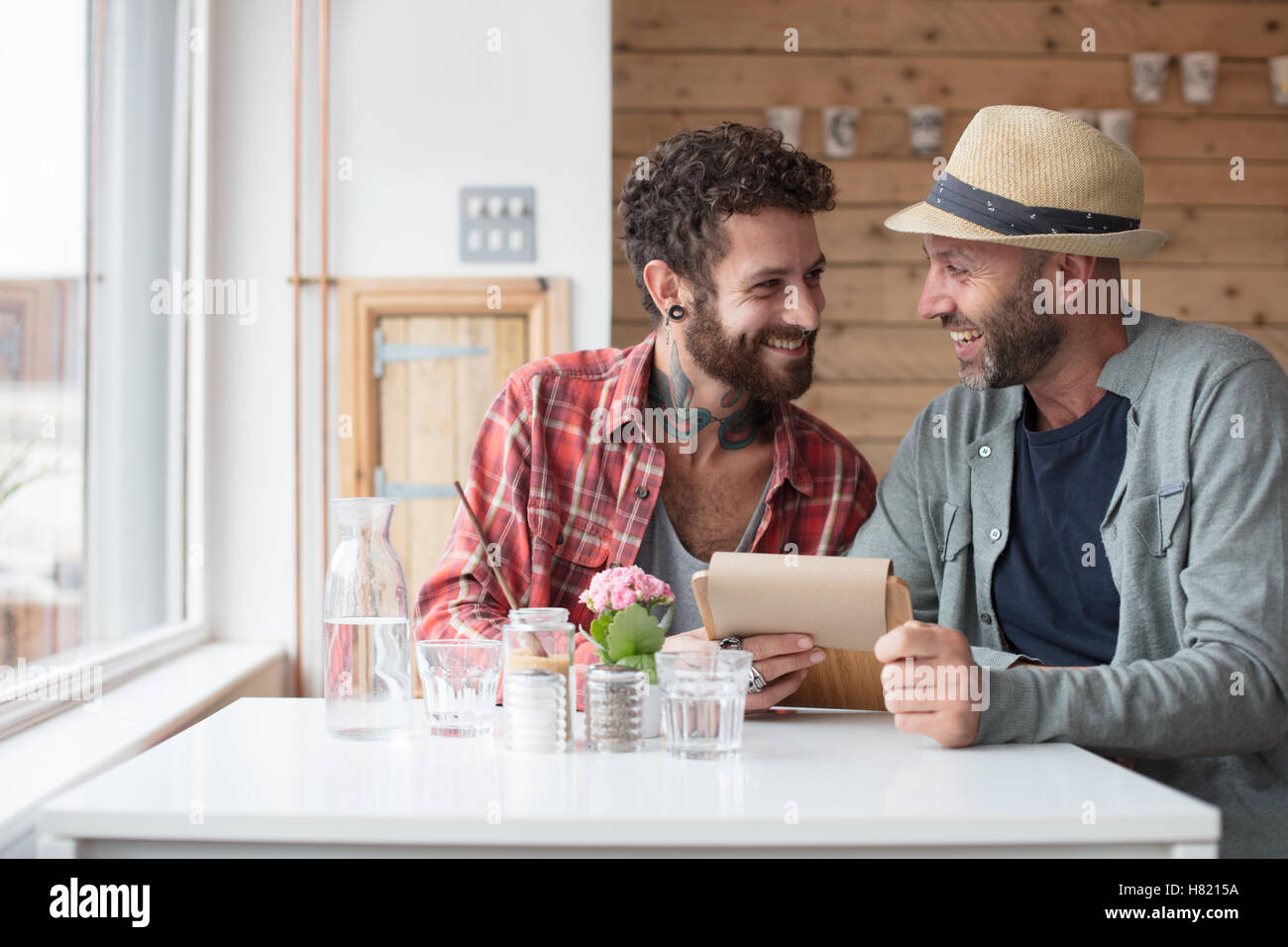 Gay couple sat viewing menu in cafe - Stock Image