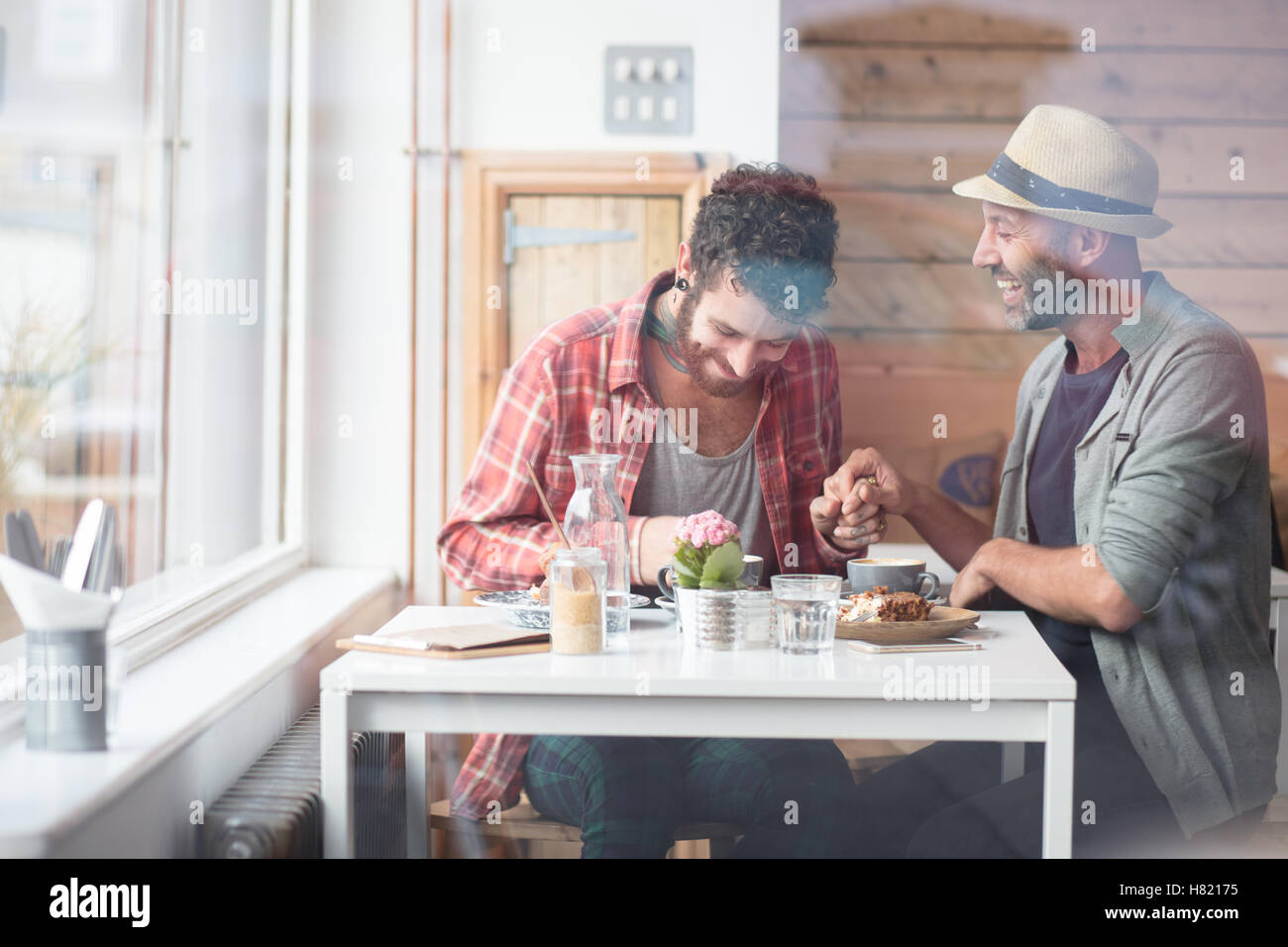 Gay couple sat holding hands in cafe Stock Photo