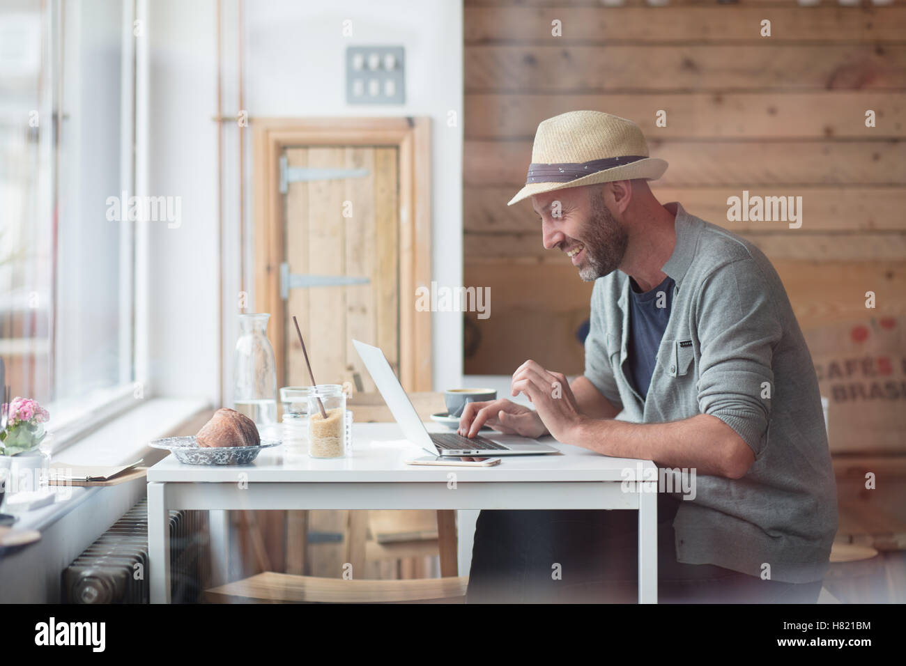Mid 30s man working at laptop in cafe - Stock Image